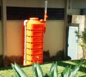 cisterna laranja sobre em um jardim ao lado do muro